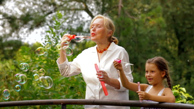 Family blowing bubbles Grandmother and granddaughter blowing bubbles in a park together granddaughter stock videos & royalty-free footage
