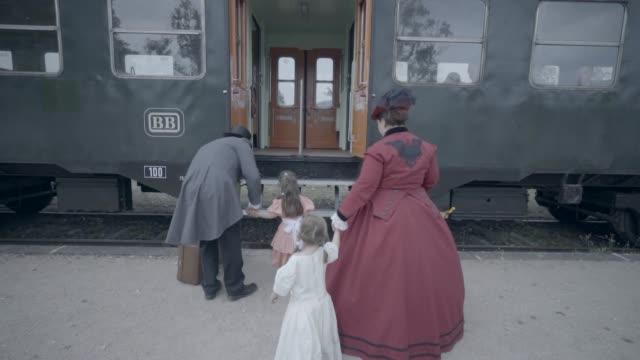family boarding old steam train - stile del xix secolo video stock e b–roll