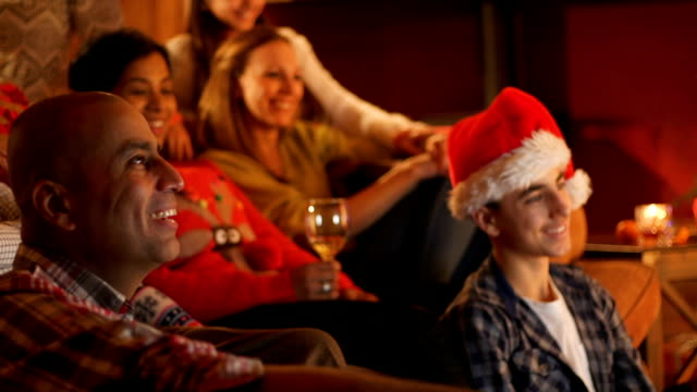 Family Bonding at Christmas A family watching the television at Christmas together all cozy on the sofa, drinking and wearing Santa hats! family watching tv stock videos & royalty-free footage