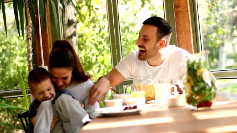 Family breakfast A handsome young family seated at the breakfast table.  The table is filled with healthy food and drinks. A little boy is wiggling in his mother's lap while she is tickling him. breakfast stock videos & royalty-free footage
