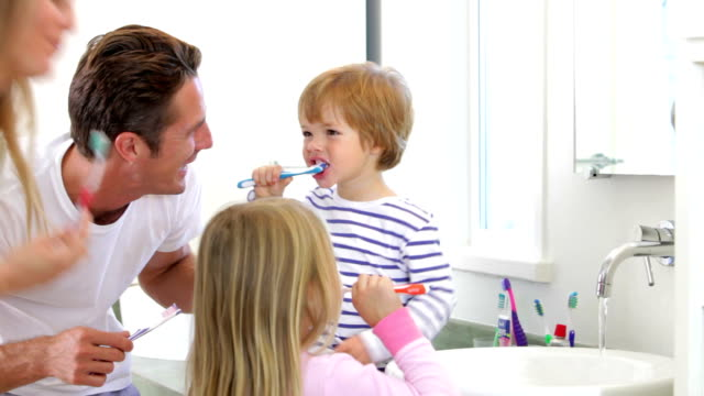Family Brushing Teeth In Bathroom Together video