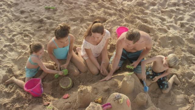 familie sandburgen an einem tropischen strand-urlaub in hawaii - spring break stock-videos und b-roll-filmmaterial