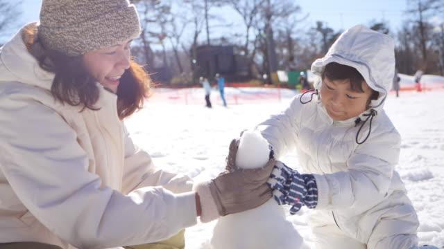 familj bygga en snögubbe - snow kids bildbanksvideor och videomaterial från bakom kulisserna