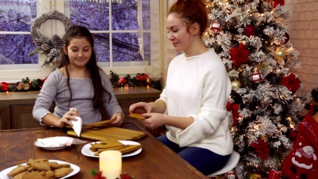 familie baut süßes lebkuchenhaus - lebkuchenhaus stock-videos und b-roll-filmmaterial