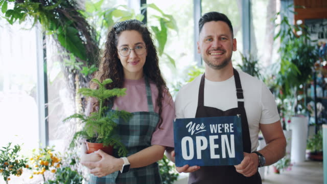 Family business owners holding open sign and plant in flower shop