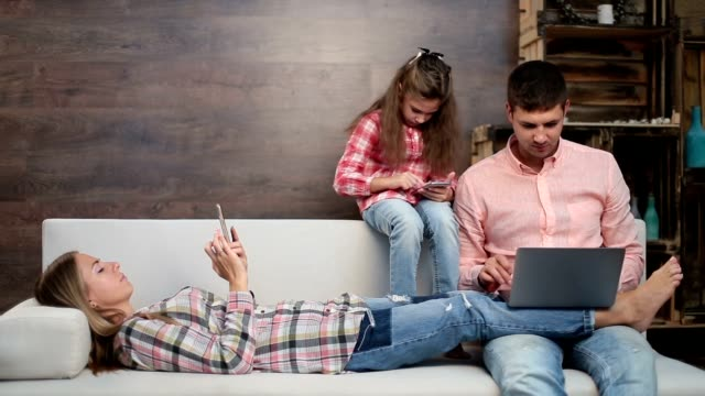 Family busy with electronic devices on sofa