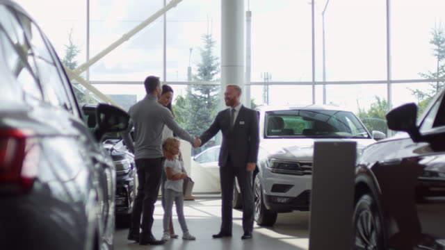 Family Buying Car and Shaking Hands with Salesman in Auto Showroom