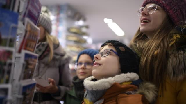 vidéos et rushes de famille achetant des cartes postales dans la boutique de souvenir - carte postale