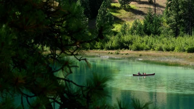 Family canoeing on a stunning mountain lake