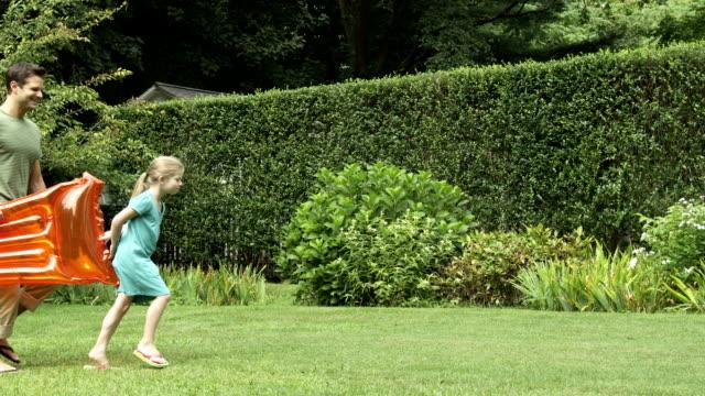 family carry inflatables in garden - kameraåkning på räls bildbanksvideor och videomaterial från bakom kulisserna