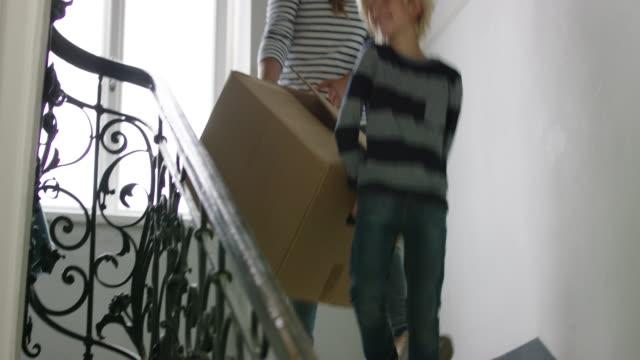 vídeos de stock e filmes b-roll de family carrying donation boxes down the stairs - economia circular