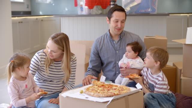 familj firar flytta in i nya hem med pizza - flyttlådor bildbanksvideor och videomaterial från bakom kulisserna