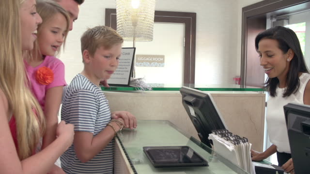 Family Checking In At Hotel Reception Using Digital Tablet video