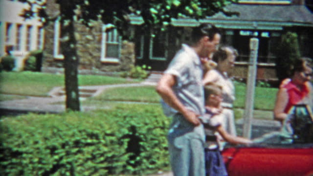 1953: Family checking out new red 53' Chevy car packing up and driving away.