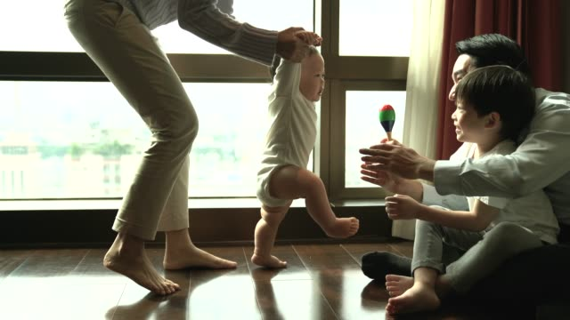 vídeos y material grabado en eventos de stock de familia, niño, infancia y concepto de la planificación de la familia - feliz bebé aprendiendo a caminar con la madre ayudan en el hogar - principios