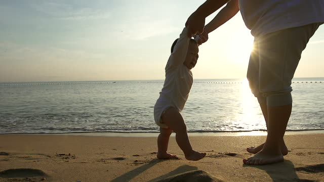vídeos de stock e filmes b-roll de family, child, childhood and parenthood concept - happy little baby learning to walk with mother help at the beach. - bebé praia