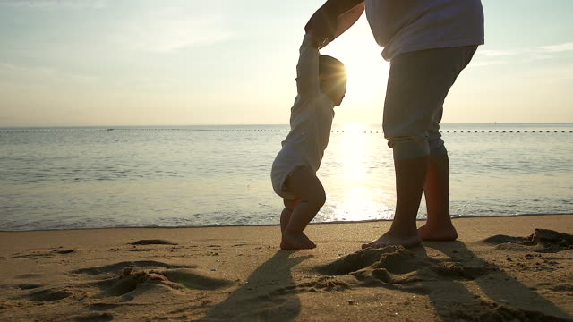 vídeos de stock e filmes b-roll de family, child, childhood and parenthood first concept - silhouette shot of baby learning to walk with mother help at the beach at the sunrise. - bebé praia