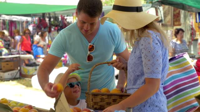 vidéos et rushes de famille choisissant peach et parlant avec sourire sur le marché en plein air, thessaloniki, grèce - chapeau
