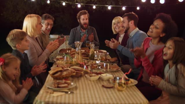 Familia de DS Palmas de las manos y cantando en barbacoa de noche - vídeo