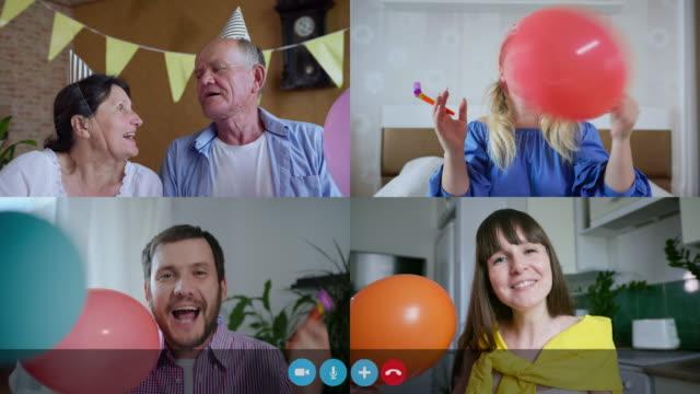 familj gratulera grattis på födelsedagen via videochatt, människor som talar på webben kameror med ballonger och festliga rör under social avståndstagande, skärmvisning - birthday celebration looking at phone children bildbanksvideor och videomaterial från bakom kulisserna