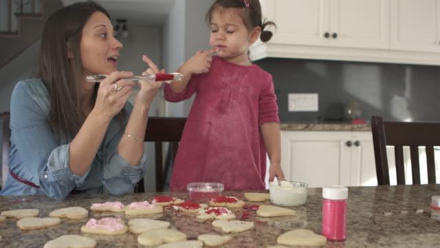 familj matlagning några kakor på kitchen counter dotter och mor - enbarnsfamilj bildbanksvideor och videomaterial från bakom kulisserna