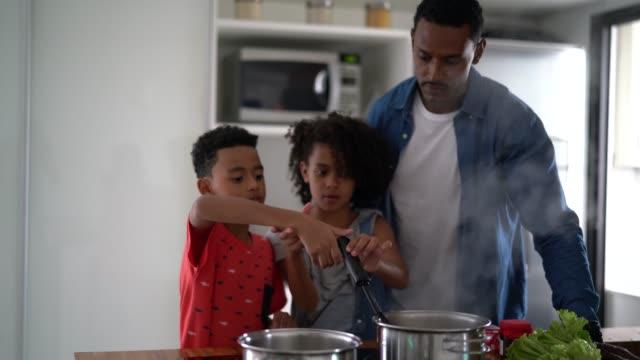familj matlagning tillsammans på kitchen - enföräldersfamilj bildbanksvideor och videomaterial från bakom kulisserna