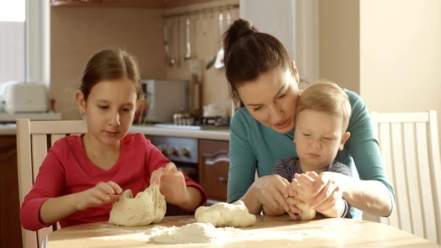 Familie kochen zusammen kneten Teig in der Küche mit Mutter Tochter und Sohn an sonnigen Tag – Video