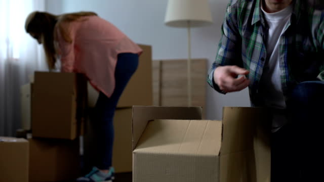 familjen par packning och ta bort sina grejer innan lägenhet översyn - flyttlådor bildbanksvideor och videomaterial från bakom kulisserna