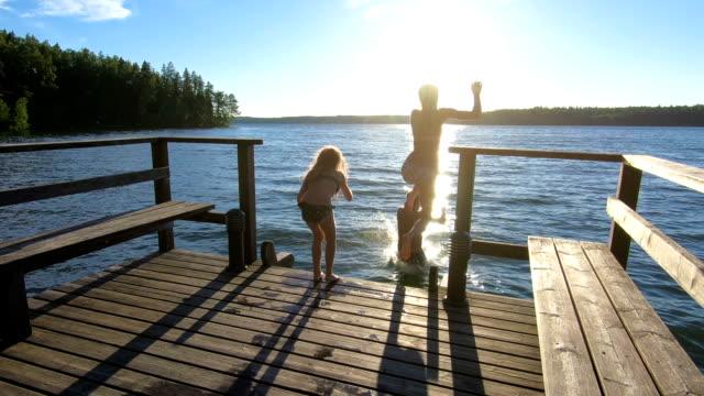 familjepar med dotter som springer på en träbrygga och hoppar ner i sjön - flod vatten brygga bildbanksvideor och videomaterial från bakom kulisserna