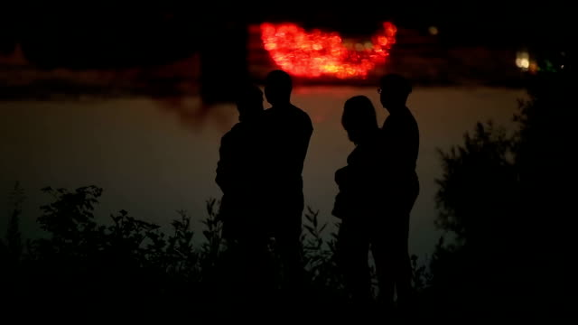 Family Couples Silhouettes with Holiday Cityscape Reflected in the Water in the Background video