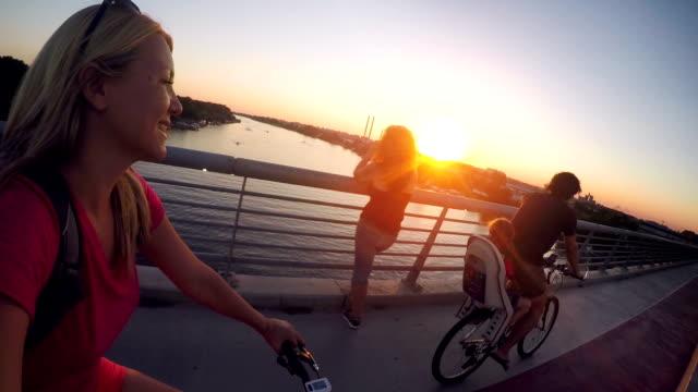 familie in der stadt bei sonnenuntergang zusammen radfahren - freizeitaktivität im freien stock-videos und b-roll-filmmaterial