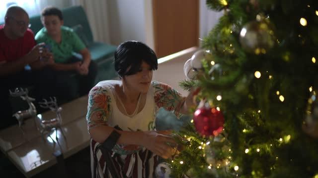 家族はクリスマスツリーを飾る - 父と息子の撮影母親 - disabilitycollection点の映像素材/bロール
