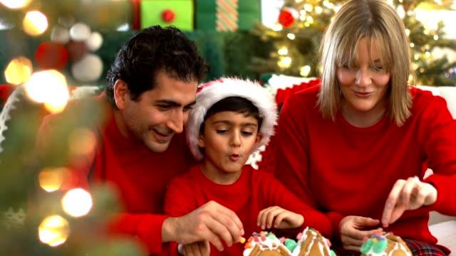 family decorating pepparkaks hus på julen - pepparkaka bildbanksvideor och videomaterial från bakom kulisserna