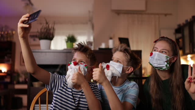 rodzina dekorowanie chirurgiczne maski na boże narodzenie - boże narodzenie filmów i materiałów b-roll