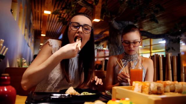 familienessen im panasiatischen restaurant. mutter und tochter essen mit holzständern rollen großes set auf sushi und brötchen auf dem restaurant-teller. - japanisches essen stock-videos und b-roll-filmmaterial