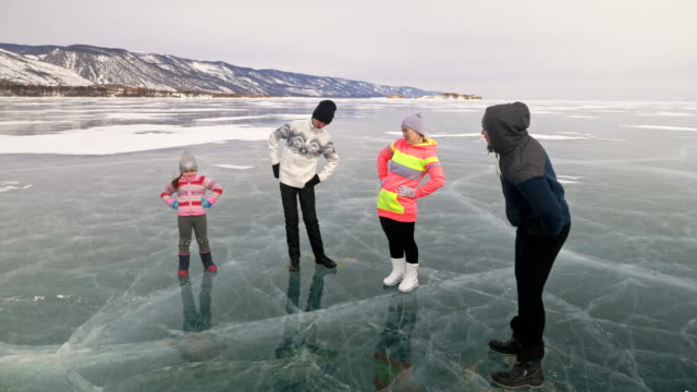 Family do sports exercise on ice in nature. Father training his family in winter. Mother daughter and son look at his training session. Children try to repeat. Standard stretch before sport. video