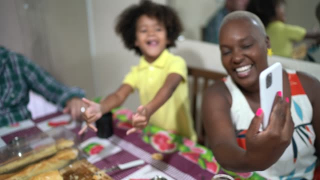 familie macht einen video-chat auf handy auf frühstück zu hause - smartphone mit corona app stock-videos und b-roll-filmmaterial