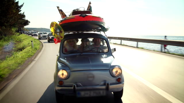 Family driving across beautiful landscape HD1920x1080: High quality produced HD Stock Footage Clip of small car filled with children toys, road toward beach  holiday stock videos & royalty-free footage