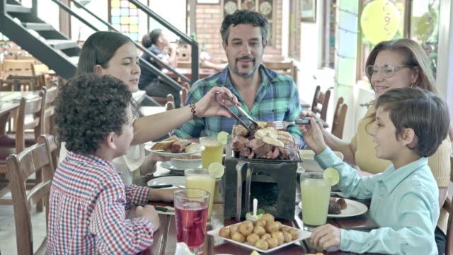 familie isst ein typisch kolumbianisches gericht in einem restaurant - lateinische schrift stock-videos und b-roll-filmmaterial