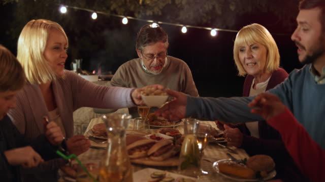 Família DS comendo na mesa de piquenique à noite - vídeo