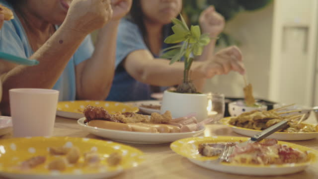 Family Eating At Table Variation Of Food On Yellow Paper Plates On Dining Table. Family Eating At Table. skewer stock videos & royalty-free footage