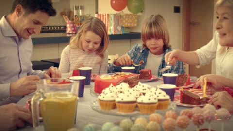 vidéos et rushes de famille manger gâteau d'anniversaire à la fête - 20 secondes et plus