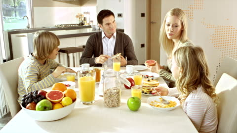 Family eating breakfast at a nicely set table Medium panning shot of mom, dad, son and daughter at a beautifully set breakfast table. They are eating and having a lively conversation for a good start of the working day. breakfast stock videos & royalty-free footage