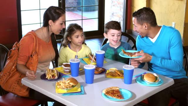 vídeos de stock e filmes b-roll de family eating lunch at amusement arcade - fast food