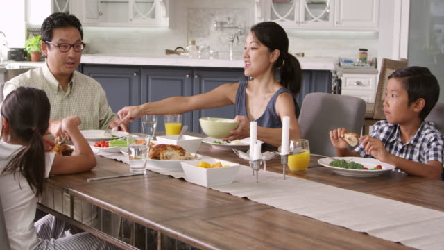 Family Eating Meal At Home Together Shot On R3D Camera tracks up from table as family sit and eat meal together east asian culture stock videos & royalty-free footage