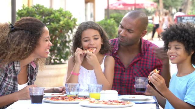 Familia comiendo comida en el restaurante al aire libre junto - vídeo