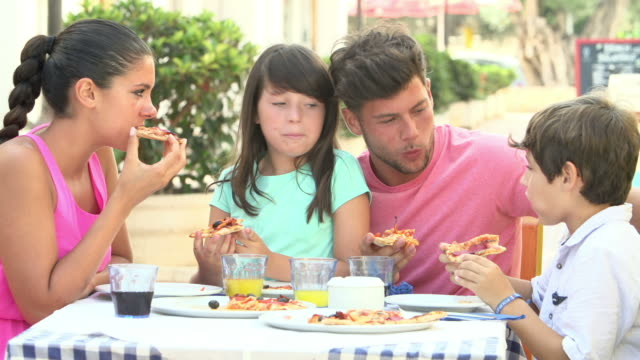 family eating meal at outdoor restaurant together - pizza stock videos and b-roll footage