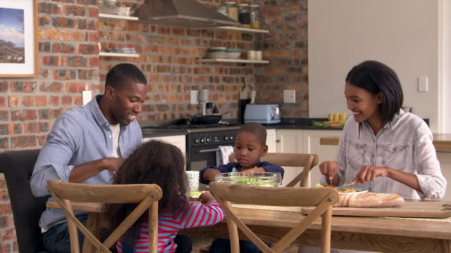 Family Eating Meal In Open Plan Kitchen Together - Vidéo