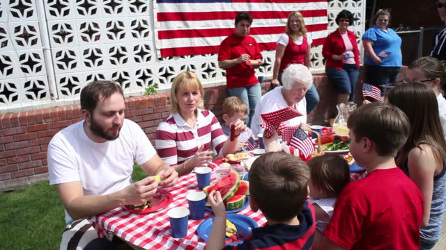 Family eating outdoor barbecue video