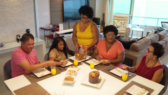 family eating panettone at home - panettone video stock e b–roll